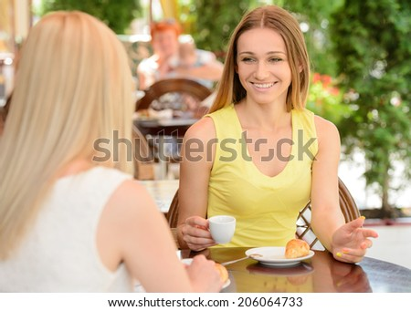 Two friends talking and drinking coffee, sitting in a cafe outdoors - stock photo