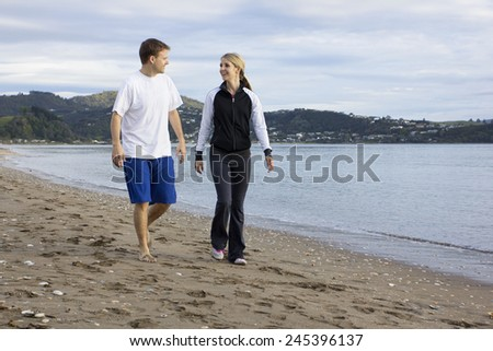 Two friends talking and walking along beach together - stock photo