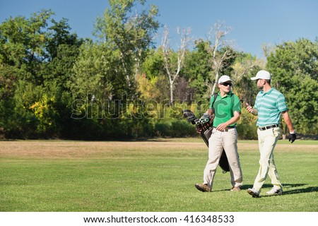 Two friends walking down the golf course - stock photo