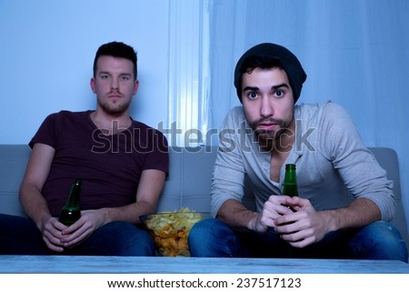 Two Friends watching passionately TV with Beer and Potato Chips.  - stock photo