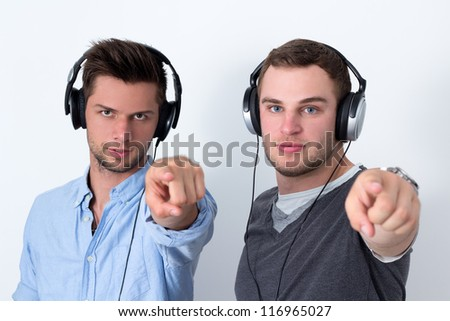 Two friends with headphone listening to music in front of a white background and pointing at camera - stock photo