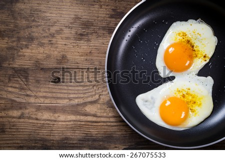 two frying eggs in pan on wooden table with copy space - stock photo