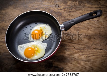 two frying eggs with spices in pan on wooden table - stock photo