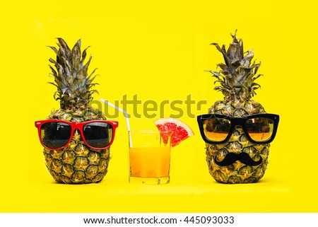 Two Fun Fashion pineapples with sunglasses and mustache with fresh tropical cocktail with fruit over yellow background. Husband and wife. Boy and girl. Vacation and travel trip concept. - stock photo