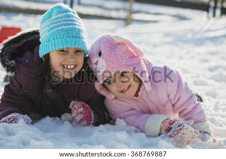 Two funny adorable little sisters playing in the snow - stock photo