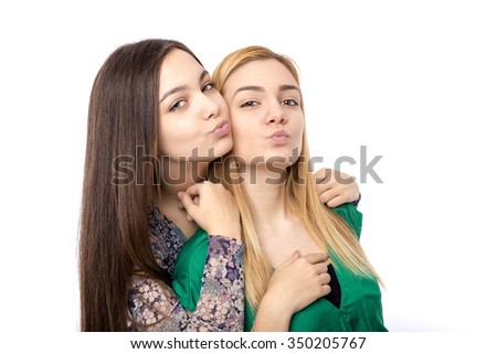 Two funny affectionate teenage friends -blonde and brunette- sending kisses over white background - stock photo