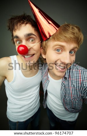 Two funny guys looking at camera and smiling crazily, fool's day series or birthday - stock photo