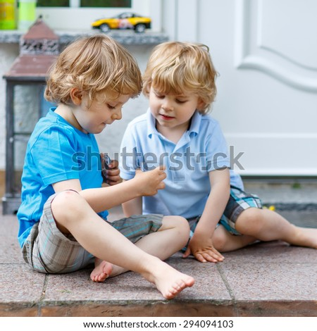 Two funny kid boys having fun and playing together in summer garden, outdoors. On warm sunny day. Happy brothers. - stock photo
