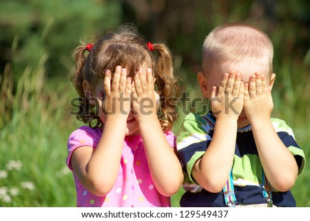 Two funny kids are playing, covering his face with his hands - stock photo