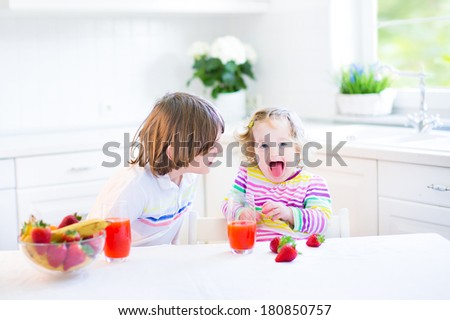 Two funny kids - school boy and his toddler sister - playing in a white sunny kitchen while having breakfast with fruit and corn flakes with strawberry - stock photo