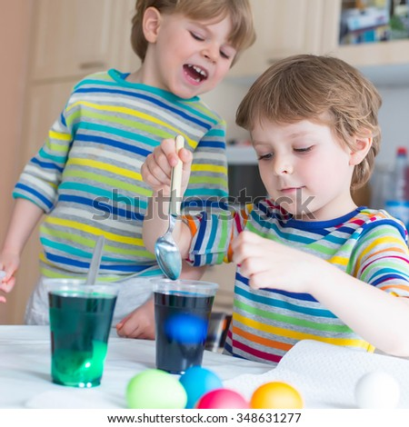 Two funny little friends boys coloring eggs for Easter holiday in domestic kitchen, indoors. Children having fun and celebrating feast. - stock photo
