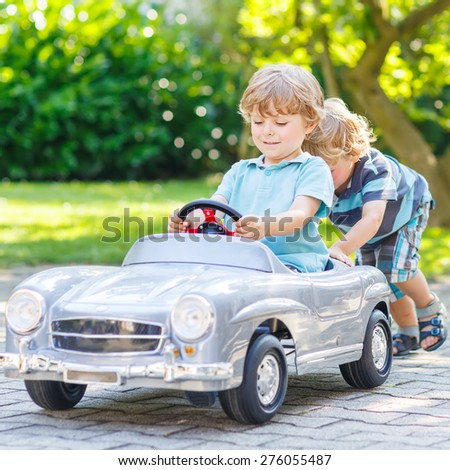 Two funny little friends playing with big old toy car in summer garden, outdoors. Active leisure with kids on warm summer day. - stock photo