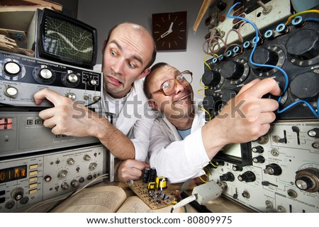 Two funny nerd scientists working at vintage technological laboratory - stock photo