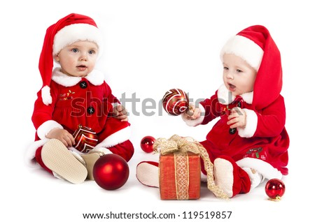 two funny small kids in Santa Claus - stock photo