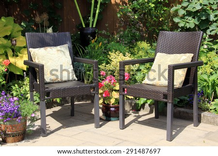 Two garden chairs surrounded by shrubs and flowers.  - stock photo