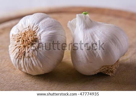 Two Garlic heads on a wood cutting board - stock photo