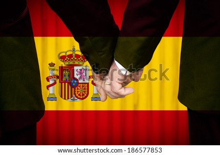 Two gay men stand hand in hand before a marriage altar featuring an overlay of the flag colors of Spain, having just been legally married under the Same-Sex Marriage legislation of that country.    - stock photo