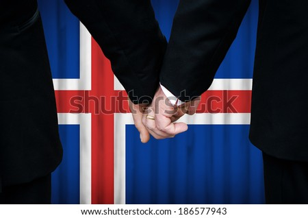 Two gay men stand hand in hand before a marriage altar featuring an overlay of the flag colors of Iceland, having just been legally married under the Same-Sex Marriage legislation of that country.    - stock photo