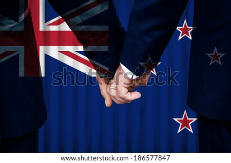 Two gay men stand hand in hand before a marriage altar featuring an overlay of the flag of New Zealand, having just been legally married under the Same-Sex Marriage legislation of that country.  - stock photo