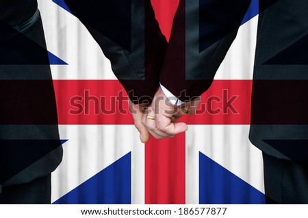 Two gay men stand hand in hand in marriage before a historic flag of Great Britain lacking St. Patrick's insignia.  As of Apr 2014 N. Ireland has not introduced legislation allowing same-sex marriage. - stock photo