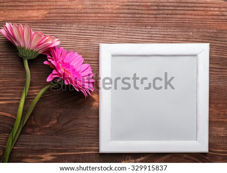 Two gerbera flowers and empty white frame on the wooden background, top view - stock photo