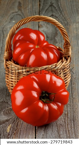 Two Giant Ripe Heirloom Tomatoes in Wicker Basket closeup on Rustic Wooden background - stock photo
