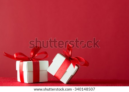 Two gift boxes wrapped with ribbon on red background - stock photo