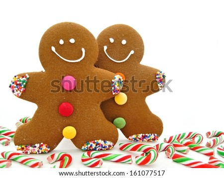 Two Gingerbread Men among scattered candy canes                     - stock photo