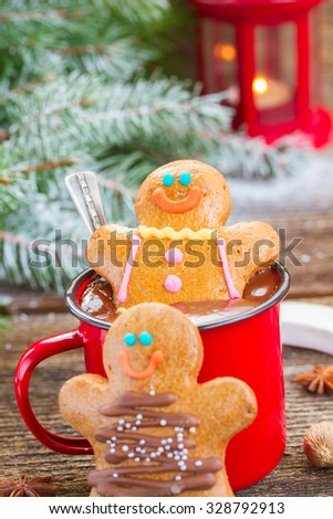 two  Gingerbread men with mug of  chocolate and glowing lantern on wood close up - stock photo