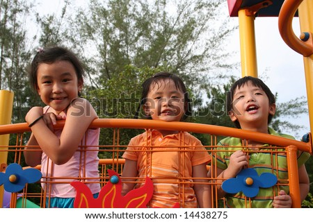 Two giris and a boy playing at the park - stock photo