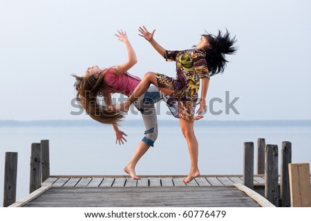 two girl  are dancing on background of water and sky - stock photo
