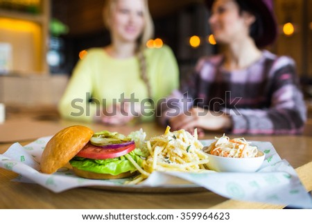 two girl - eating hamburger and drinking  in a fast food diner; focus on the meal - stock photo