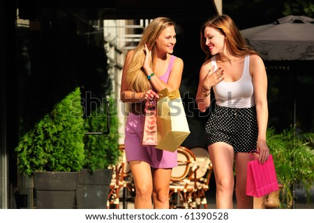 two girl friends having fun on a shopping spree in the city - stock photo