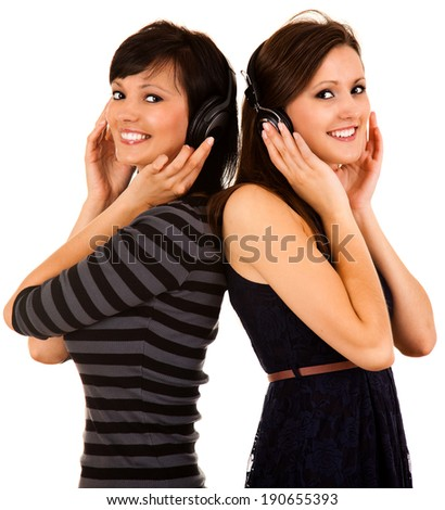 two girl friends in heaphones, white background - stock photo