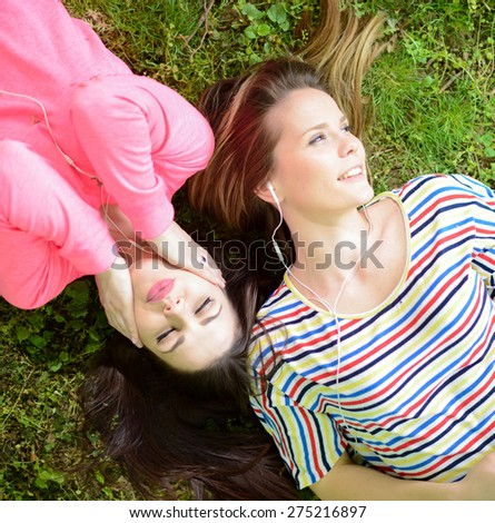 Two girl friends listening to music while lying on grass during summer day - stock photo