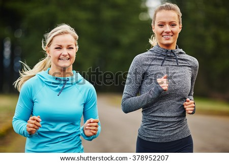two girl friends smiling and running together - stock photo
