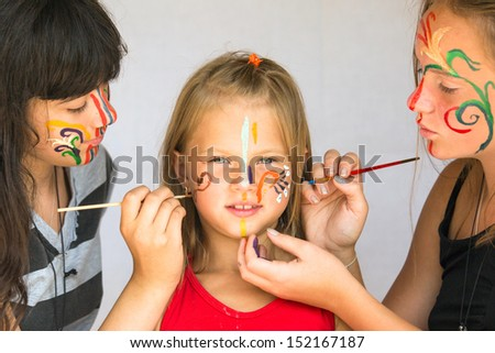 Two girl playing with painting with little sister. - stock photo