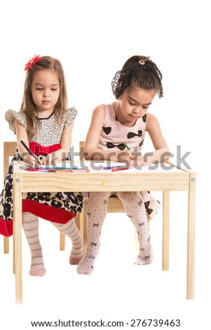 Two girl sitting on chairs and drawing at table isolate don white background - stock photo