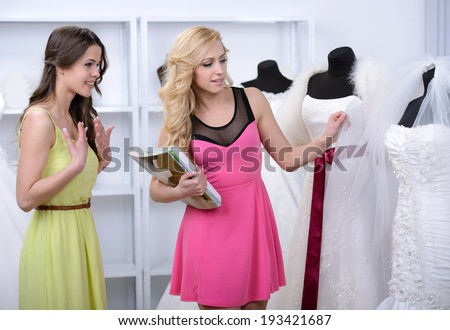 Two girlfriends - bridesmaids- having fun - looking for dresses for wedding - stock photo