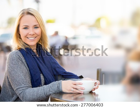 Two girlfriends getting coffee together outside - stock photo