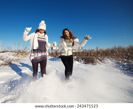 Two girlfriends have fun at beautiful winter day - stock photo