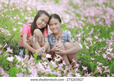 two girlfriends having fun in flower field - stock photo