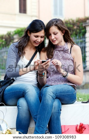 Two girlfriends in park with a mobile phone, italy - stock photo