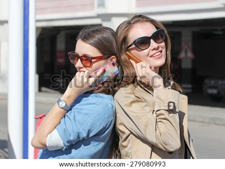 Two girlfriends mobile phone speaking back by back. Outdoors, sunny day - stock photo