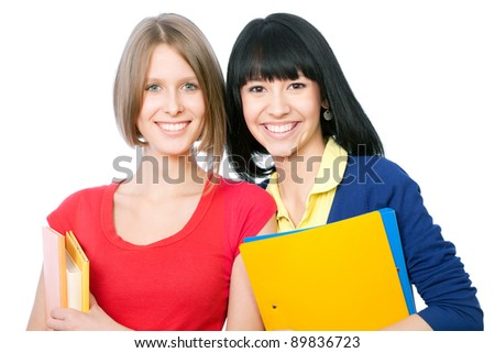 Two girlfriends smiling students and looking at camera - stock photo