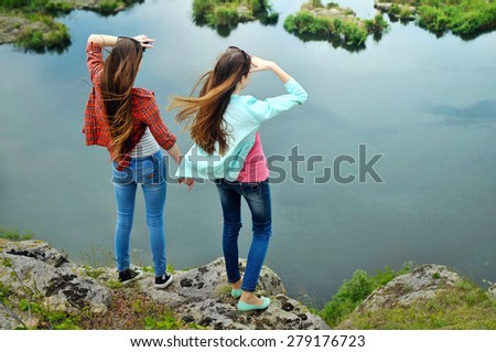 Two girlfriends standing on the rock above the water - stock photo