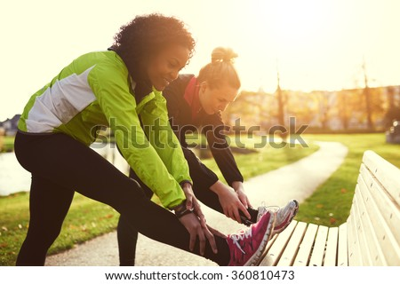 Two girlfriends stretching in sunny park - stock photo
