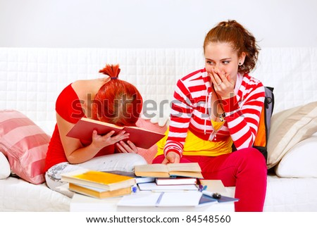 Two girlfriends tired while studying at living room - stock photo