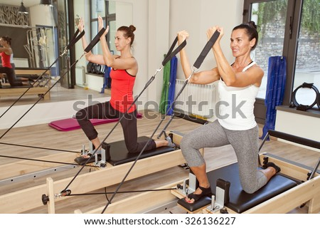 Two girls are exercising pilates using pilates device reformer - stock photo