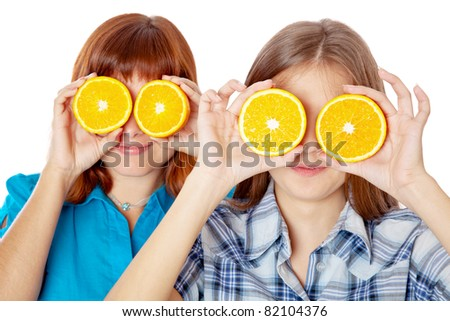 Two girls are looking through oranges. Isolated on white background - stock photo